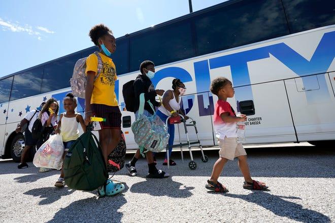Evacuees walk to board buses Tuesday, Aug. 25, 2020, in Galveston, Texas. The evacuees are being taken to Austin, Texas, as Hurricane Laura heads toward the Gulf Coast.