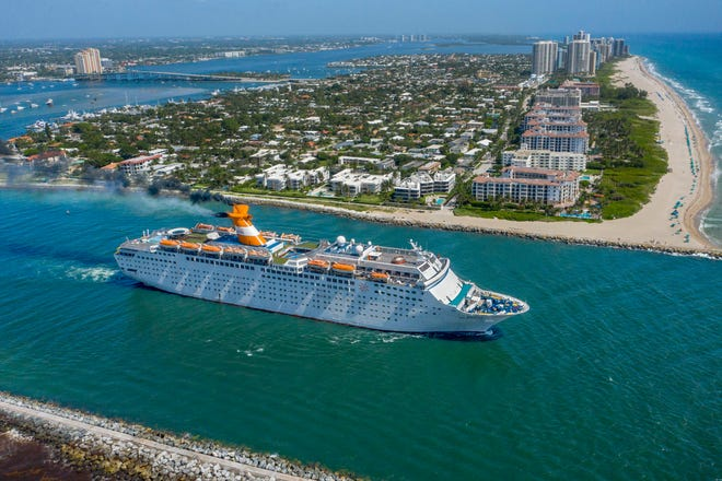 The Grand Celebration cruise ship sails through the Lake Worth Inlet between Palm Beach and Singer Island, Florida, after leaving the Port of Palm Beach. [GREG LOVETT/palmbeachpost.com]