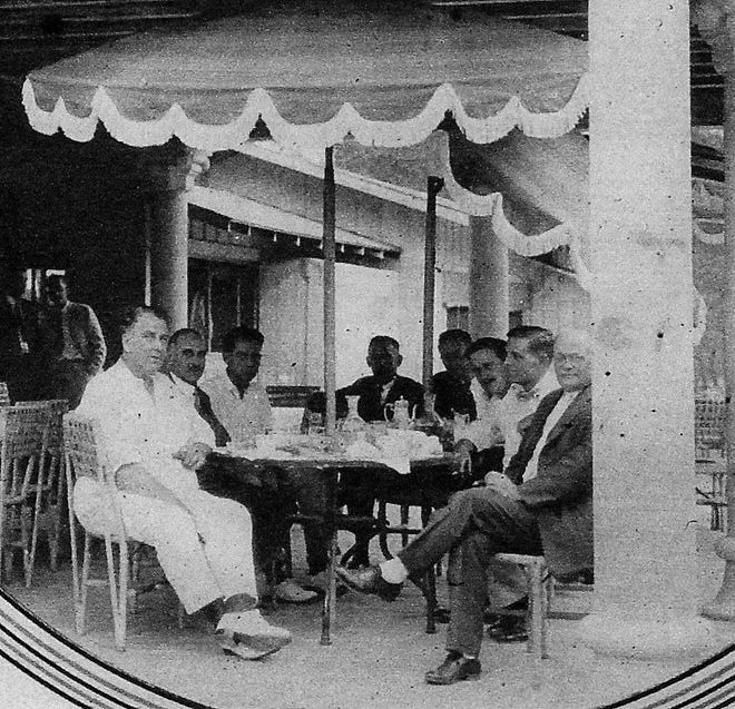 The late society architect Addison Mizner, pictured at left front, was a sought-after lunch and dinner partner due to his colorful storytelling and wit. The photograph was taken in 1926 on the porch of the then-Administration Building in Boca Raton.