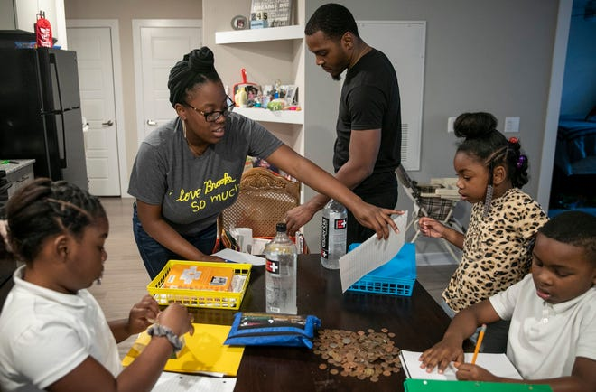 Amber Fowler, a teacher at Brooke Elementary School, and her husband Jacolby Scott, give lessons to their children, Jaliyah Scott, 8, from left, Jamiyah Scott, 5, and Javon Scott, 7, at their apartment in South Austin in March. Kids learn who they are and how to cope within their families.  [JAY JANNER/AMERICAN-STATESMAN]