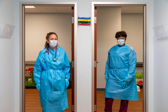 Pediatrician Dr. Julie Konowitz-Sirkin, left, and medical assistant Katrina Lockhart stand outside two exam rooms dedicated for children that need to be examined for COVID-19 at Just for Kids Pediatric west of Boynton Beach, Florida on March 19. [GREG LOVETT/palmbeachpost.com]