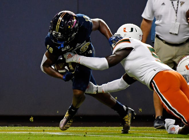 Miami Hurricanes safety Amari Carter (5) tackles FIU Golden Panthers wide receiver Shemar Thornton (19) during last season's game.