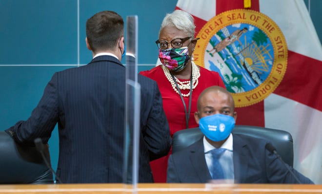 County administrator Verdenia Baker speaks to Mayor Dave Kerner before the Aug. 25 commission meeting where Phase 2 of reopening was discussed. At right is commissioner Mack Bernard. [LANNIS WATERS/palmbeachpost.com]