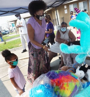 Dorothy Beattie helps Maleah Brown find at Teddy bear during Community Care Day Tuesday hosted by the Sierra Vista Housing Authority.  [CALIXTRO ROMIAS/THE STOCKTON RECORD]