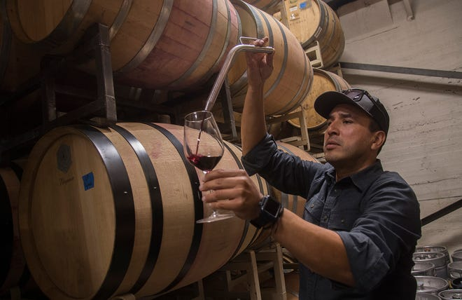 Gerardo Espinosa, owner of Anaya Vineyards, draws some wine in the barrel room of his new location at the former Toasted Toad Cellars in downtown Lodi. [CLIFFORD OTO/THE STOCKTON RECORD]