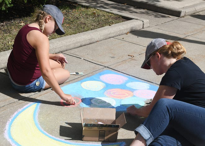 Holley Reynolds, 11, and her mother Lisa Reynolds, of Edinburg, work on a piece together at Chalk Fest in downtown Ravenna.