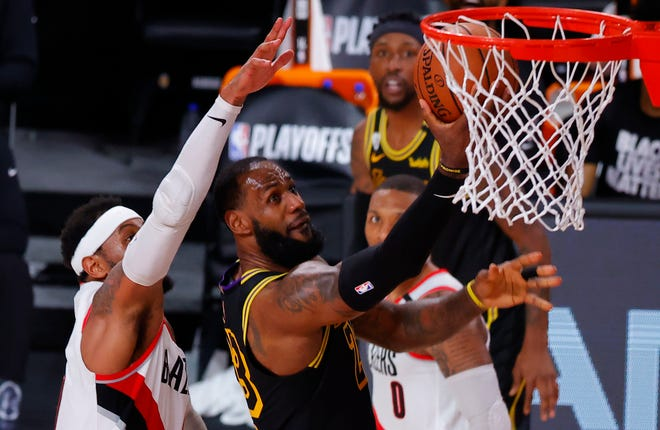 Los Angeles Lakers' LeBron James (23) shoots against Portland Trail Blazers' Carmelo Anthony, left, during the second quarter of Game 4 of an NBA basketball first-round playoff series on Monday. [Kevin C. Cox/Pool Photo via AP]