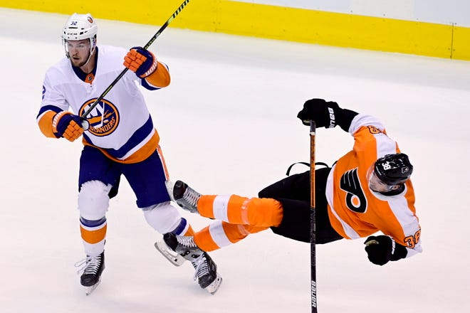 New York Islanders defenseman Adam Pelech (3) levels Philadelphia Flyers center Derek Grant (38) during first-period NHL Stanley Cup Eastern Conference playoff hockey game action in Toronto on Monday. [Frank Gunn/The Canadian Press via AP]