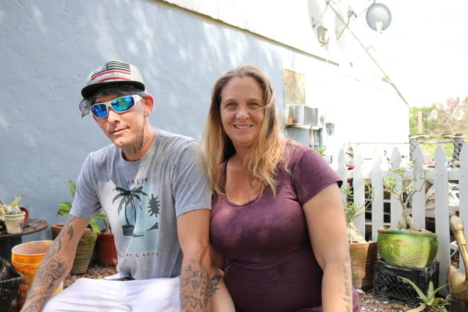 Shyla Robinett, 39, and her boyfriend, Robert Delarue, 40, sit outside their rental house in North Port Monday evening. Robinett's plant business, Plants by Shyla, has been on pause since the couple moved to North Port, aside from setting up at a local market in Englewood each Sunday.