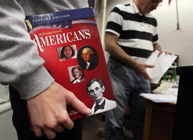 A student holds a history textbook.