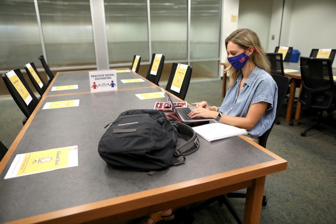 Sela Dougherty, a first-year law student, takes some time to study at a table marked for social distancing in accordance with Covid-19 safety protocols, in the law library at the Levin College of Law at the University of Florida.
