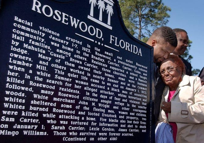 A survivor of the Rosewood massacre, Robie Allenetta Mortin, is comforted after the unveiling of a historical marker in 2004.