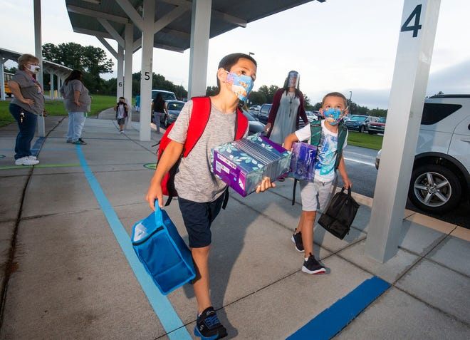 Elementary school students arrive for their first day of school Aug. 24 in Marion County, while wearing masks and carrying tissues for their classrooms.