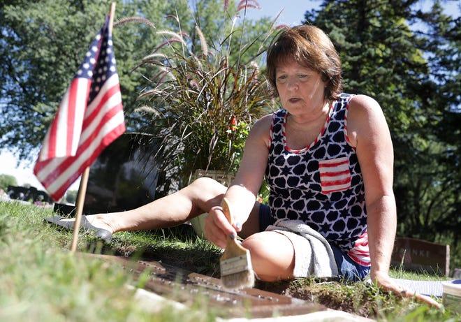 Army veteran Laurel Sternhagen cleans and repairs veteran's grave markers at Riverside Cemetery in Appleton.