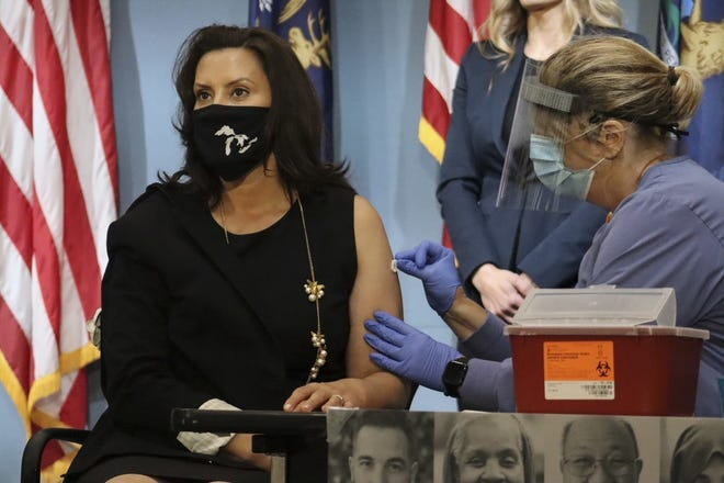 Gov. Gretchen Whitmer gets a flu shot during a press briefing on August 25, 2020.
