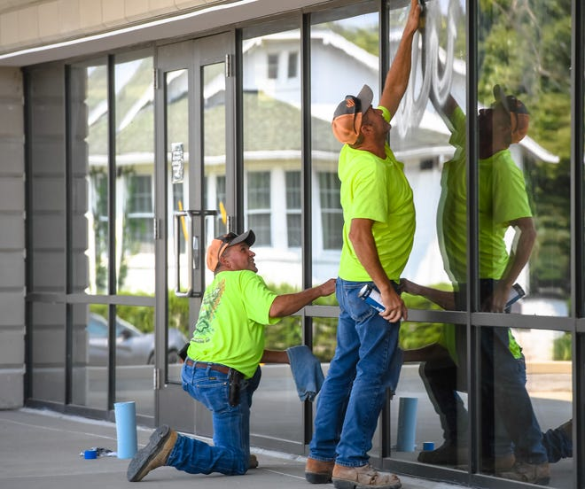 Wayne McDowell, left, and Ricky Blanford, with Empire Contracting, wash windows on the Henderson County Public Library's new addition Tuesday afternoon, August 25, 2020. After being closed for five months due the pandemic, the library will open for in-person services 9 a.m. Thursday.