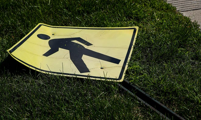 A pedestrian cross walk sign lays on the ground at the intersection of Fall Creek Parkway Drive and Illinois Street in Indianapolis, Tuesday, August 20, 2020.