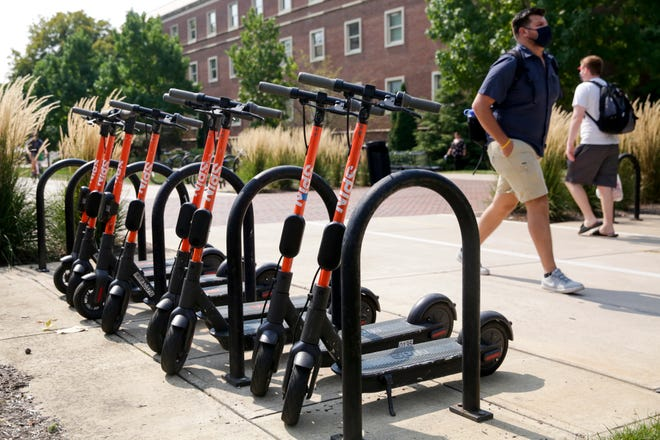 A row of Spin Scooters sit park in a bike rack by the Gateway to the Future archway at Purdue University, Tuesday, Aug. 25, 2020 in West Lafayette.