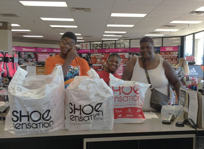 Du'Jywan Lewis, left, and Maurice Smith Jr., center, were all smiles after Shaquita Lewis, right, purchased new shoes for school last week during the annual Cents for Shoes campaign. Cents for Shoes chairperson Robin Rick said the generosity of Marion County residents made it possible for more than 500 local children to have new shoes for school this year.