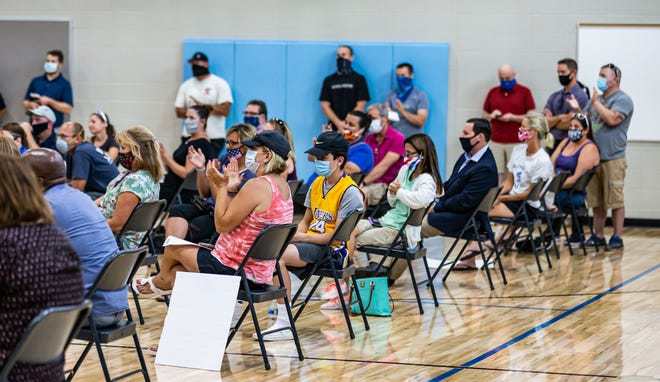 Community members applaud comments made by a parent to Oak Creek-Franklin School District board members, regarding the decision to move the district's reopening from in-person to virtual, during a school board meeting at Edgewood Elementary School on Monday, August 24, 2020.