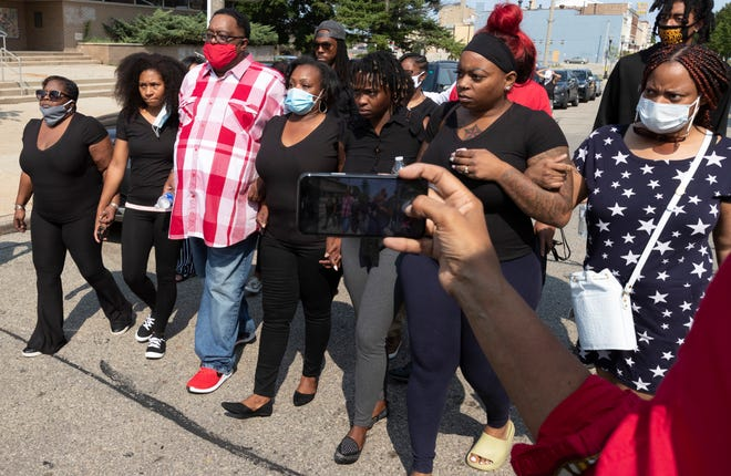 Jacob Blake Sr., third from left, and Julia Jackson, fourth from left, the parents of Jacob Blake, walk with family members to a news conference Tuesday in Kenosha. Their son, Jacob Blake, was shot in the back by a Kenosha police officer Sunday.