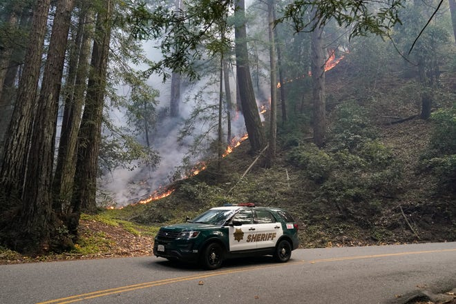 A police vehicle is seen under a forest being burned by the CZU August Lightning Complex Fire Monday, Aug. 24, 2020 near in Bonny Doon, Calif. (AP Photo/Marcio Jose Sanchez)
