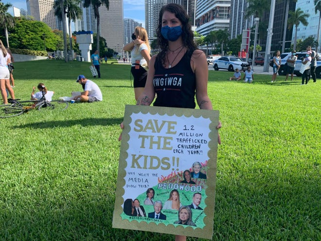 Jenn Luizzi, a 27-year-old QAnon supporter from Deerfield Beach, holds a sign at Bayfront Park during a child sex trafficking rally in Miami on Aug. 22, 2020. (Martin Vassolo/Miami Herald/TNS)