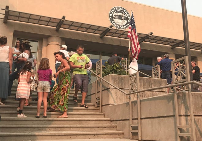 People pushing for businesses and schools to reopen amid the coronavirus pandemic line up outside the Shasta County Administration Center before the start of the Board of Supervisors' meeting on Tuesday, Aug. 25, 2020.