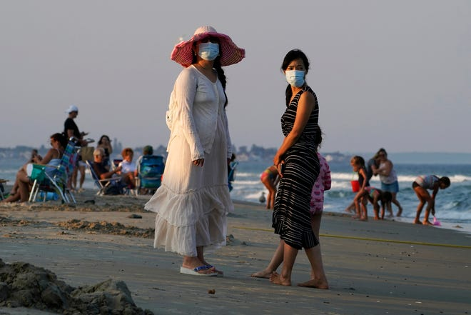 FILE - In this Aug. 11, 2020, file photo, women wear masks to help prevent the spread of coronavirus at the end of a beach day in Ogunquit, Maine. The number of Americans newly diagnosed with the coronavirus is falling — a development experts credit at least partly to increased wearing of masks — even as the outbreak continues to claim nearly 1,000 lives in the U.S. each day. (AP Photo/Robert F. Bukaty, File)