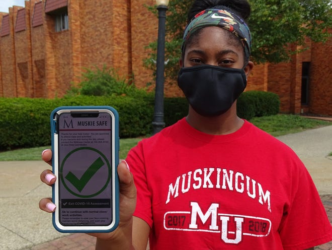 After completing the self-health assessment on Muskingum University's Muskie Safe app, 20-year-old engineering student Camryn Woodley demonstrates how she uses the check mark as a pass into all of MU's facilities.
