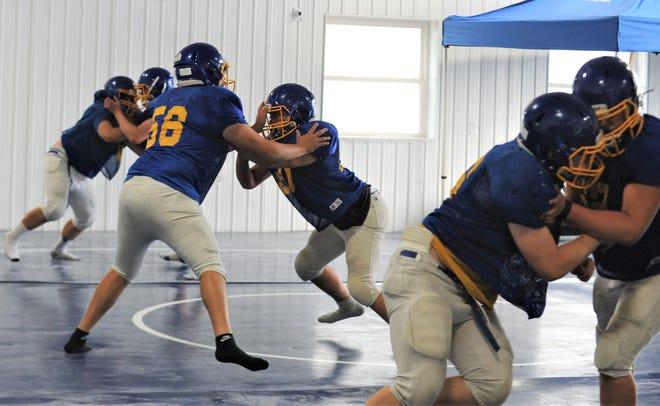 West Muskingum linemen work through a blocking drill during Tuesday's practice. The Tornadoes were forced inside due to inclement weather.