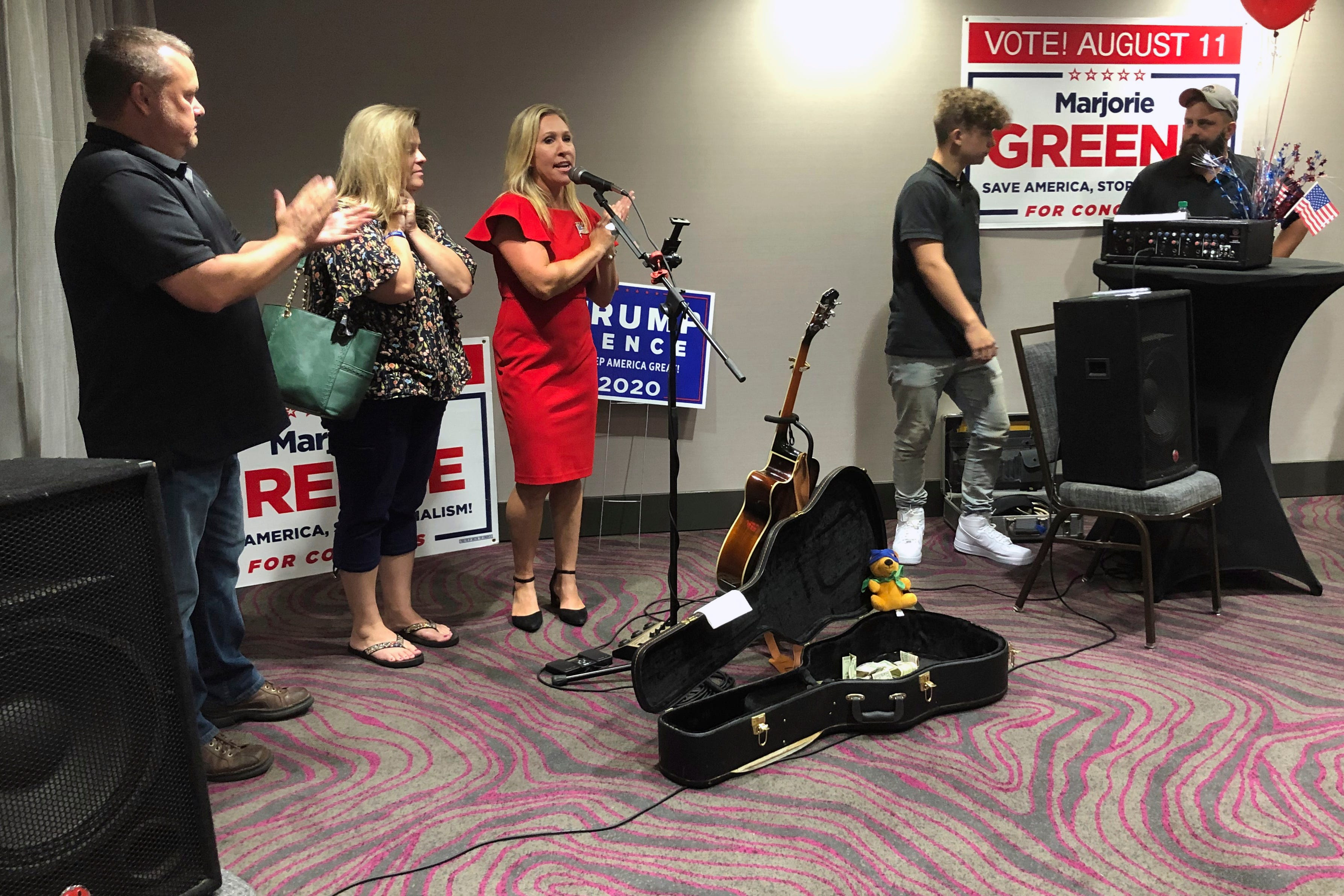 Marjorie Taylor Greene, third from left, claps with her supporters at a watch party event, on Tuesday, Aug. 11, 2020, in Rome, Georgia, where she won the GOP nomination for northwest Georgia's 14th Congressional District. Greene, a construction executive, has been criticized for promoting racist videos and adamantly supporting the far-right QAnon conspiracy theory.