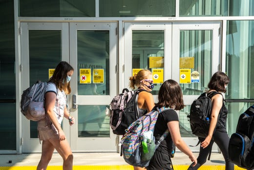 Students wearing face masks walk past doors marked with COVID-19 related warnings at the Seamans Center during the first day of in-person classes for the fall semester amid the novel coronavirus pandemic, Monday, Aug. 24, 2020, on the University of Iowa campus in Iowa City, Iowa.