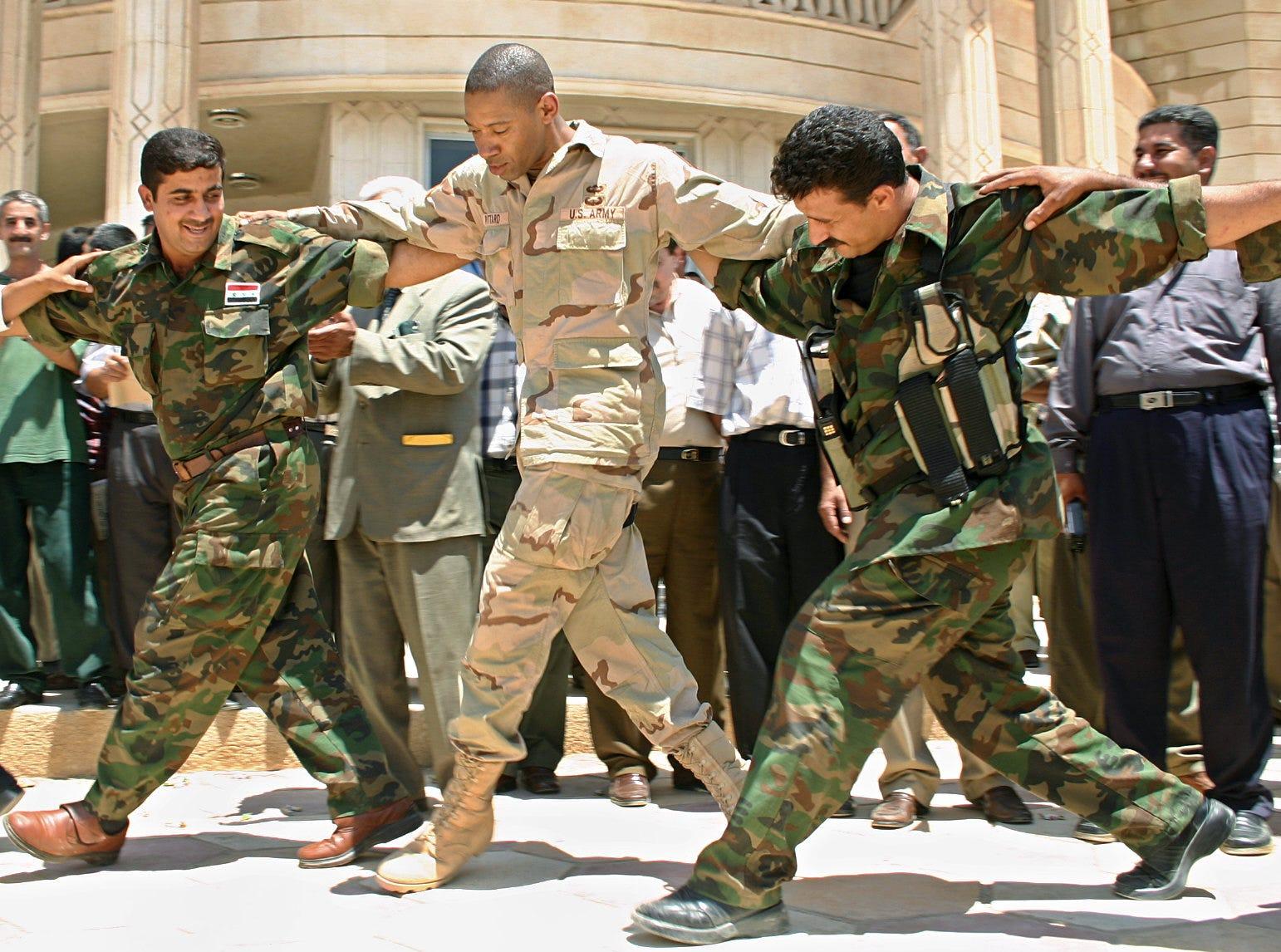 Dana Pittard dances with Iraqi national guardsmen during an Iraqi flag-raising ceremony in Baquba, northeast of Baghdad, on July 6, 2004.