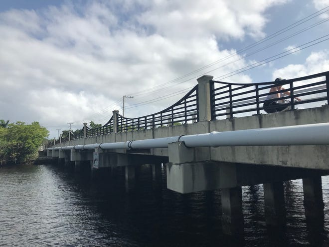 A cyclist rides across the Loxahatchee River Road bridge Tuesday morning in Jupiter.