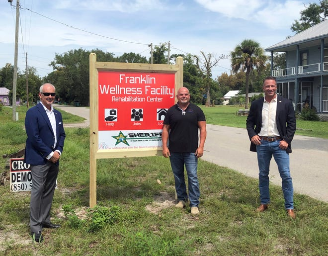 Mike Watkins of Big Bend Community Based Care, at left, assistant Mike Kemp, center, and Sheriff A.J. Smith stand with the sign for the new wellness facility.