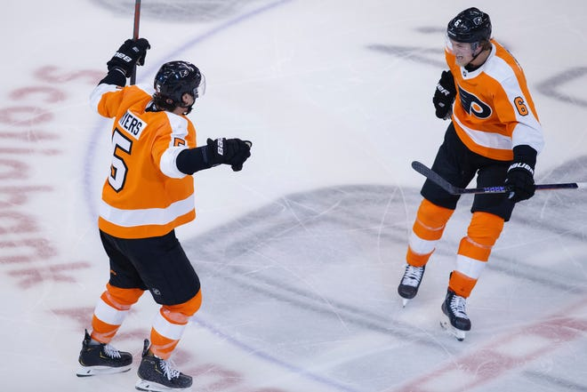 Philadelphia Flyers defenceman Philippe Myers (5) celebrates his game-winning goal in overtime with teammate defenceman Travis Sanheim (6) during overtime in an NHL Stanley Cup Eastern Conference playoff hockey game against the New York Islanders in Toronto, Ontario, Wednesday, Aug. 26, 2020. (Cole Burston/The Canadian Press via AP)