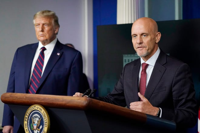 President Donald Trump listens as Dr. Stephen Hahn, commissioner of the U.S. Food and Drug Administration, speaks during a media briefing in the James Brady Briefing Room of the White House Sunday in Washington