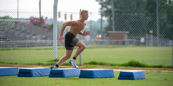 Asheboro's Logan  Richardson runs a high step bag drill during a summer workout on Aug. 10.