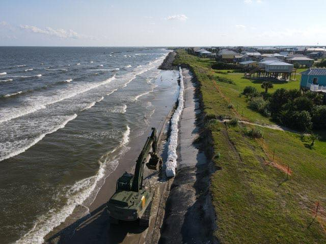 On Saturday, the Louisiana National National Guard began placing the 3-by-3 foot white sacks between the water line and a section of the island's west-side storm surge levee damaged by Tropical Storm Cristobal in June.