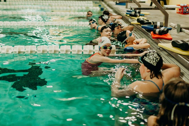 Young swimmers rest during a swim training at the indoor pools at Muletown Rec in Columbia, Tenn.