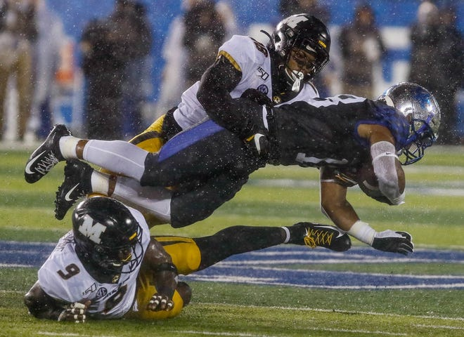 Missouri's Joshuah Bledsoe (18) and Tyree Gillespie (9) tackle a Kentucky receiver during a Southeastern Conference game last season.