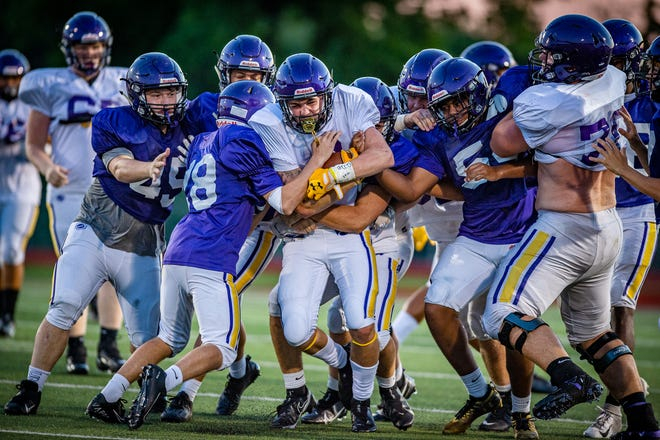 A host of Blue Springs tacklers tries to take down receiver Isaac Harkness, center, during their intrasquad scrimmage last Friday.