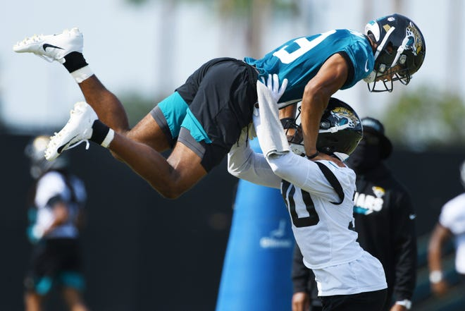 Jaguars rookie safety J.R. Reed lifts wide receiver Collin Johnson, a fellow rookie, during drills at a recent training camp practice session.