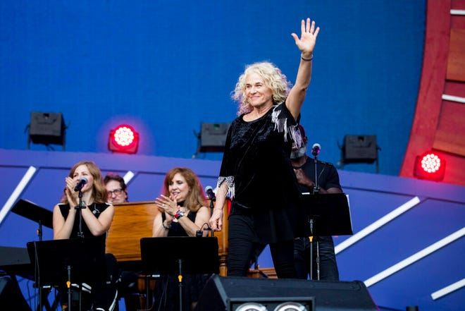 "FILE - In this Sept. 28, 2019, file photo, Carole King waves to the crowd as she takes the stage at the 2019 Global Citizen Festival in New York. Poised over the piano, King was set to play ""I Feel the Earth Move"" during a recent virtual fundraiser for Joe Biden when the Democratic presidential nominee himself beat her to it. ""On my playlist, Carole!"" Biden proclaimed, holding up his phone and letting a few seconds of the song blast."