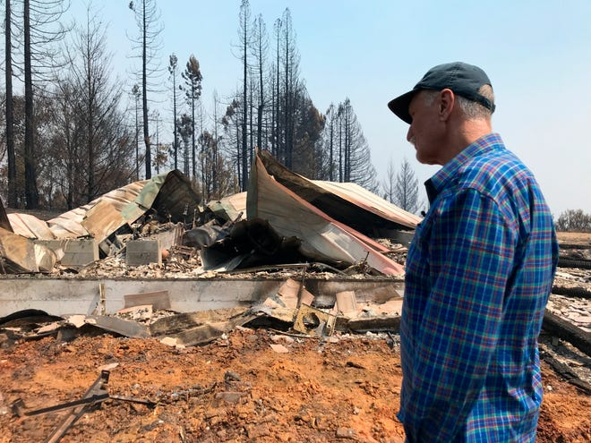 Charles Christianson, a 67-year-old retired school teacher, returns to his destroyed home after a wildfire in Guerneville, Calif., on Tuesday.