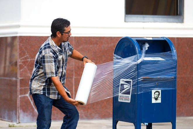 A United State Postal Service Employee covers a mailbox with plastic wrap after removing the last mail from it as the island prepares for possible impact from Hurricane Laura, Tuesday, Aug. 25, 2020, in Galveston. The plastic wrap signals that the final mail has been cleared from the box and prevents people from placing more mail inside in case of flooding.