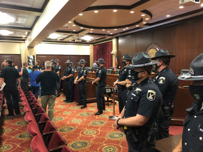 Idaho State Police form a row in a committee meeting room in the Idaho Statehouse in Boise, Idaho, on Tuesday. One person was taken into custody and lawmakers abandoned the room after spectators at a House committee meeting at the Idaho Statehouse became disruptive. The committee left the room as at least a dozen Idaho State Police formed a shield between them and the crowd of more than 100.
