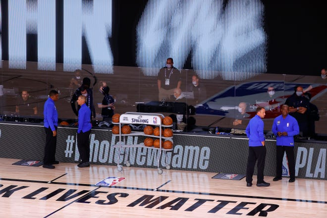 Referees stand on an empty court before the start of a scheduled game between the Milwaukee Bucks and the Orlando Magic for Game 5 of an NBA basketball first-round playoff series on Wednesday in Lake Buena Vista.