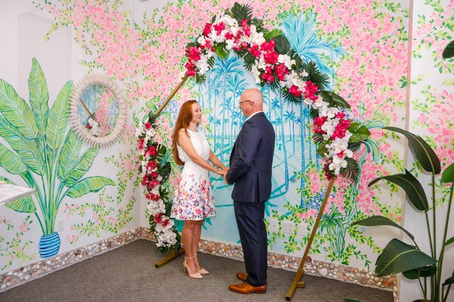 Alex Korogodsky of Boca Raton and his bride, Viktoria Kharkina, get married Aug. 21 in the new Lilly Pulitzer-designed marriage ceremony room at the Main Courthouse in downtown West Palm Beach. The room's decor features flowing palm trees, bright pink flowers and delicate orchids hand-painted by a Lilly Pulitzer Print Studio artist. [DAMON HIGGINS/palmbeachdailynews.com]